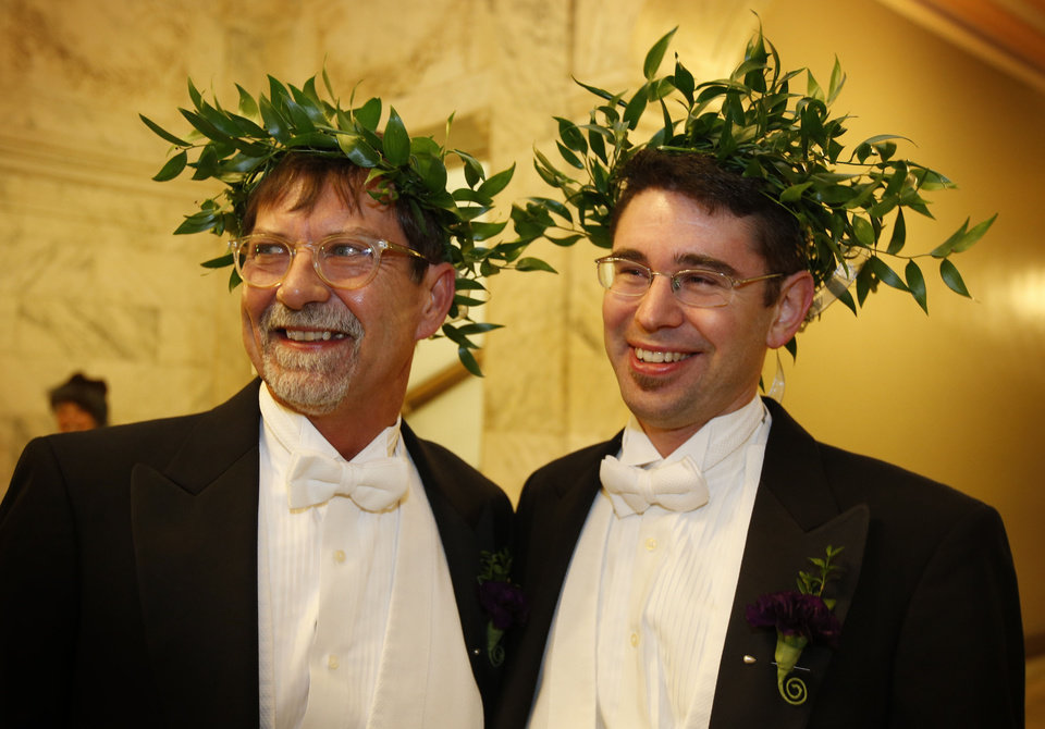 Photo - Steven Jones, left, and Jamous Lizotte wear laurel wreaths as they arrive at City Hall to obtain a marriage license, Friday, Dec. 28, 2012, in Portland, Maine. Same-sex couples in Maine will be allowed to marry as a new law goes into effect at 12:01 AM Saturday, Dec. 29, 2012.(AP Photo/Robert F. Bukaty)