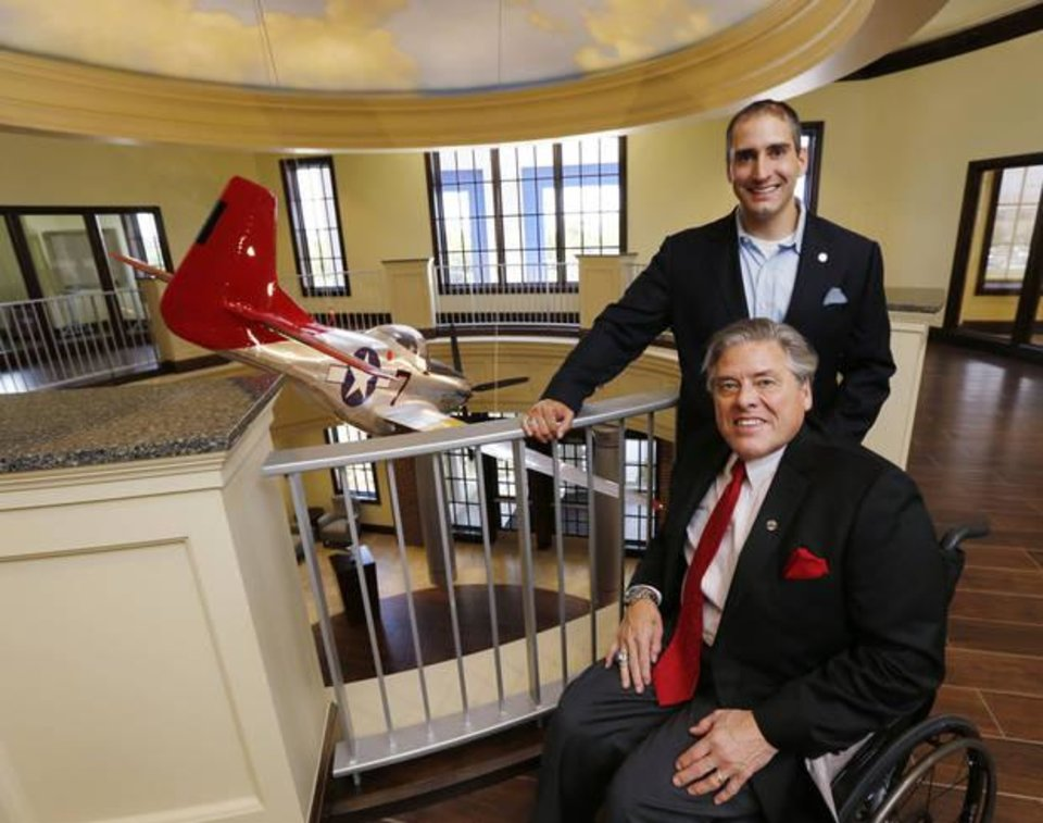 Photo -  Delaware Resource Group Chairman and CEO Phil G. Busey Sr., front, and Philip Busey Jr., senior vice president and chief communications officer, show the atrium and replica P-51 Mustang fighter plane that honors the Tuskegee Airmen, at the new DRG headquarters at 3220 Quail Springs Parkway. [PHOTO BY PAUL HELLSTERN, THE OKLAHOMAN]