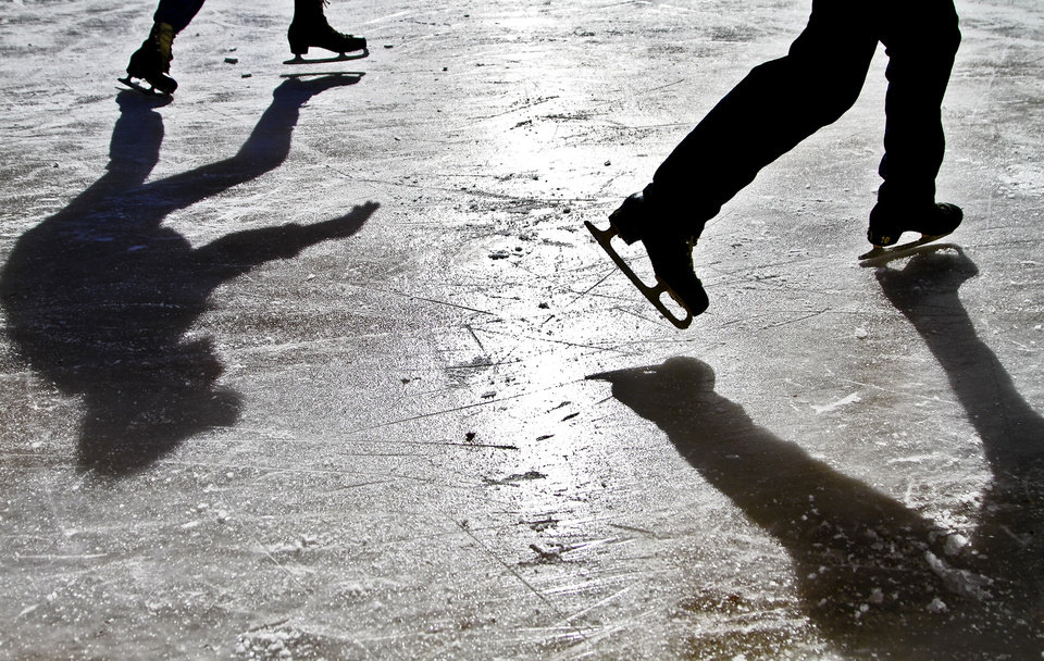 Skaters cast shadows across the ice while taking advantage of the cold temperatures at the Edmond Outdoor Skating Rink on Wednesday, Dec. 26, 2012, in Edmond, Okla.   Photo by Chris Landsberger, The Oklahoman