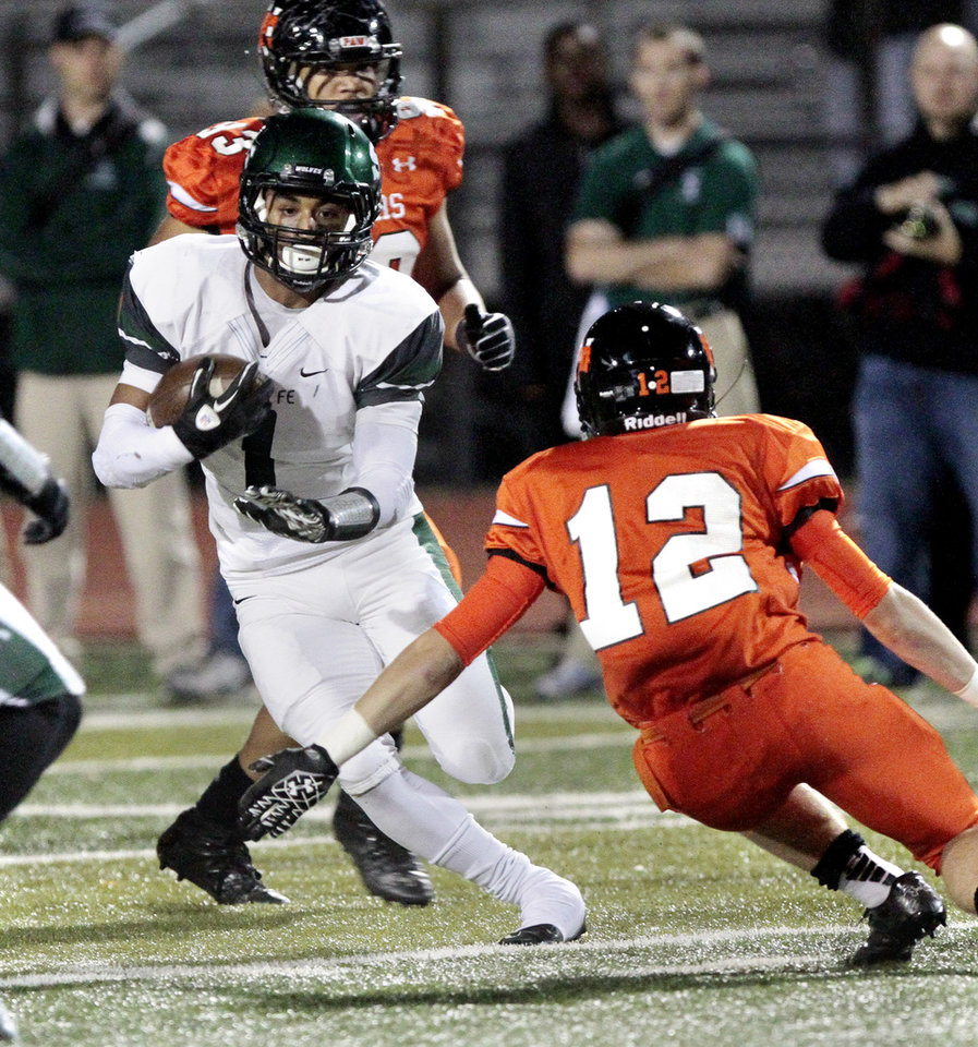 Santa Fe\'s Phillip Sumpter avoids the tackle attempt by Norman\'s Gavin Nadeau (12) in high school football as the Norman High School Tigers play the Edmond Santa Fe Wolves on Friday, Oct. 19, 2012 in Norman, Okla. Photo by Steve Sisney, The Oklahoman