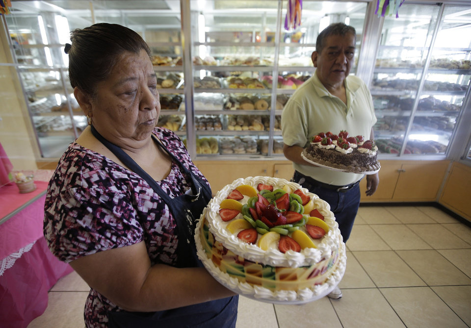 Photo - In this July 31, 2014, photo, Concepcion Flores, owner of Panaderia Flores, holds a gelatina cake on Salt Lake City's west side. Panaderia Flores offers sweet breads, pineapple or pumpkin empanadas and tamales. (AP Photo/Rick Bowmer)