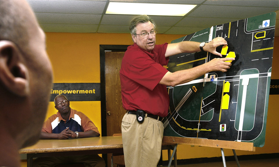 Photo - Driving instructor Ted Vitamvas uses a magnetic board to teach various traffic scenarios bus drivers will encounter during a classroom training session  at the district's transportation center in northeast Oklahoma City, Thursday,  Aug. 7, 2008.   BY JIM BECKEL, THE OKLAHOMAN ORG XMIT: KOD