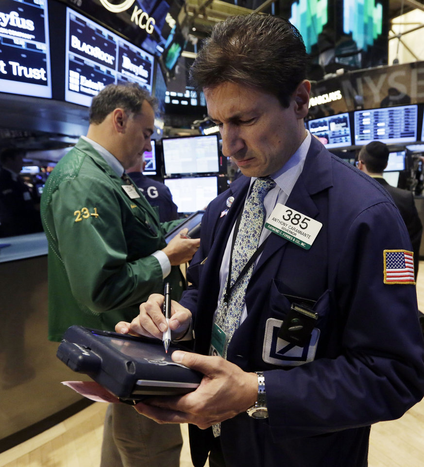 Photo - Trader Anthony Carannante, right, works on the floor of the New York Stock Exchange Monday, July 22, 2013. The stock market is opening mixed after McDonald's reported poor quarterly earnings. (AP Photo/Richard Drew)
