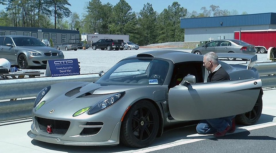 Photo - In this photo made from video, Atlanta Motorsports Park member David Wert inspects his Lotus Exige S240 in the pit area April 17, 2014, in Dawsonville, Ga., prior to a run on the 2-mile road racing course. The members-only facility provides racing services for the well-heeled exotic car owner. (AP Photo/Johnny Clark)