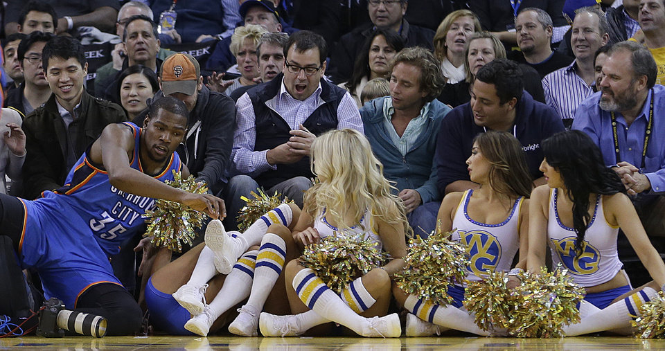 Oklahoma City Thunder's Kevin Durant (35) falls into the Golden State Warrior girls during the second half of an NBA basketball game against the Golden State Warriors Wednesday, Jan. 23, 2013, in Oakland, Calif. (AP Photo/Ben Margot) ORG XMIT: OAS107