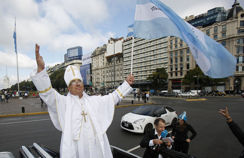 Photo - Daniel Francisco Venezia, an Argentina soccer fan dressed as Pope Francis, waves the Argentine flag the morning of the final Brazil World Cup match between Argentina and Germany, in Buenos Aires, Argentina, Sunday, July 13, 2014. (AP Photo/Jorge Saenz)