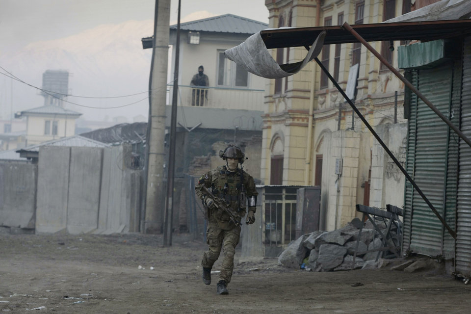 A Norwegian soldier with the NATO-led forces runs near the Kabul traffic police headquarters during insurgents' attack,  in Kabul, Afghanistan, Monday, Jan. 21, 2013. Taliban insurgents wearing suicide vests attacked the headquarters before dawn Monday, police said, and eyewitnesses heard numerous explosions while a gun battle was still raging nearly four hours later. (AP Photo/Musadeq Sadeq)