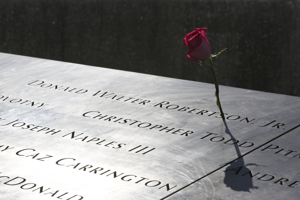 Photo - A rose is placed next to the name of a victim of the terrorist attacks on the World Trade Center at the North Pool of the National September 11 Memorial and Museum, Friday, Sept. 6, 2013, in New York. Construction is racing ahead inside the museum as the 12th anniversary of the Sept. 11, 2001 attacks draws near. Several more large artifacts have been installed in the cavernous space below the World Trade Center memorial plaza. (AP Photo/Mary Altaffer)