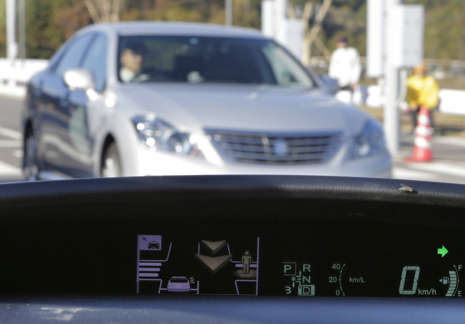 Photo -   A human sign and an arrow pop up on a dashboard display to notify the driver of a pedestrian's presence and an approaching car at the coming intersection during a demonstration of Toyota Motor Corp.'s Intelligent Transport System at its Higashi-Fuji Technical Center in Susono, southwest of Tokyo, Monday, Nov. 12, 2012. Toyota is testing out safety systems using cars that communicate with each other and with the roads they are on in a just-completed facility in Japan, the size of three baseball stadiums. (AP Photo/Koji Sasahara)