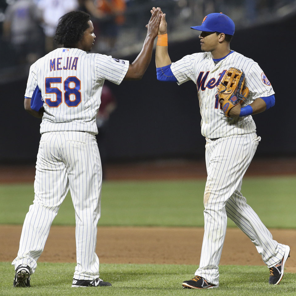 Photo - New York Mets relief pitcher Jenrry Mejia (58) and center fielder Juan Lagares celebrate after a baseball game against the Atlanta Braves, Tuesday, Aug. 26, 2014, in New York. The Mets won 3-2. (AP Photo/John Minchillo)