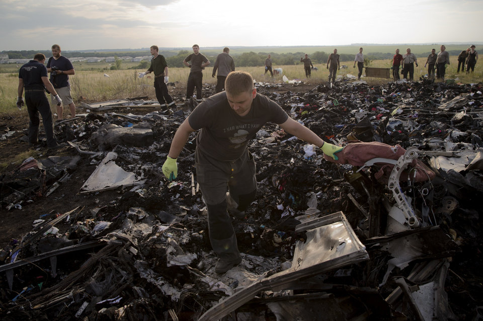 Photo - A man looks for the remains of victims in the debris at the crash site of Malaysia Airlines Flight 17 near the village of Hrabove, eastern Ukraine, Saturday, July 19, 2014. World leaders demanded Friday that pro-Russia rebels who control the eastern Ukraine crash site of Malaysia Airlines Flight 17 give immediate, unfettered access to independent investigators to determine who shot down the plane. (AP Photo/Vadim Ghirda)
