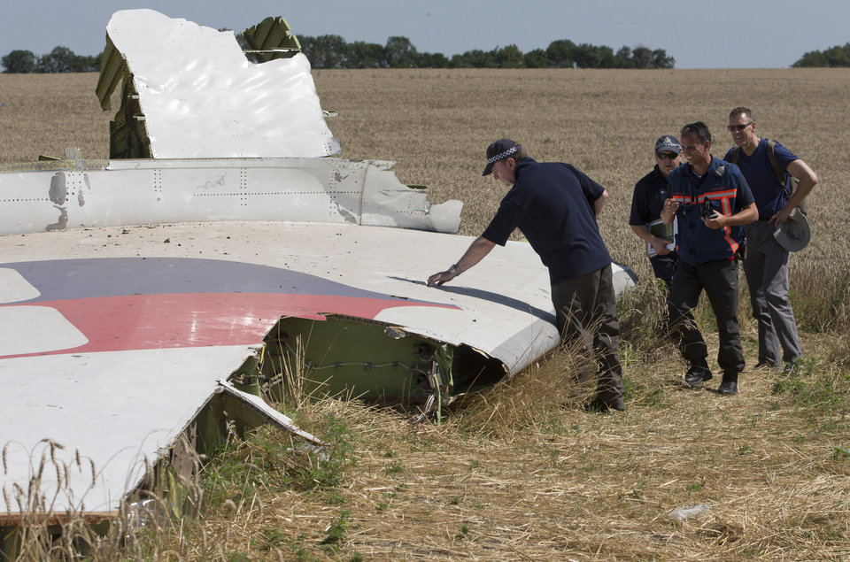 Photo - Australian and Dutch investigators examine a piece of the Malaysia Airlines Flight 17 plane, near the village of Hrabove, Donetsk region, eastern Ukraine Friday, Aug. 1, 2014. The investigators from the Netherlands and Australia plus officials with the Organization for Security and Cooperation in Europe traveled from the rebel-held city of Donetsk in 15 cars and a bus to the crash site outside the village of Hrabove. Then they started setting up a base to work from at a chicken farm. The investigative team's top priority is to recover human remains that have been rotting in midsummer heat of 90 degrees (32 degrees Celsius) since the plane went down on July 17.  (AP Photo/Dmitry Lovetsky)