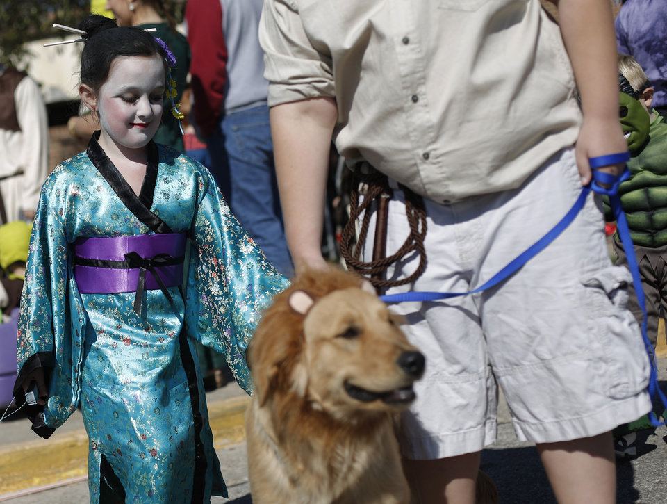 Peyton Stein, 7 of Yukon, dress as a Geisha, pets Harley during a dog and child costume show at the Yukon Community Center in Yukon, Okla., Saturday, Oct. 27, 2012.  Photo by Garett Fisbeck, The Oklahoman