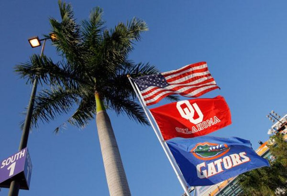 Photo -  Flags for the United States, University of Oklahoma and University of Florida fly in the parking lot before the BCS National Championship college football game between the University of Oklahoma Sooners (OU) and the University of Florida Gators (UF) on Thursday, Jan. 8, 2009, at Dolphin Stadium in Miami Gardens, Fla.   PHOTO BY NATE BILLINGS, THE OKLAHOMAN