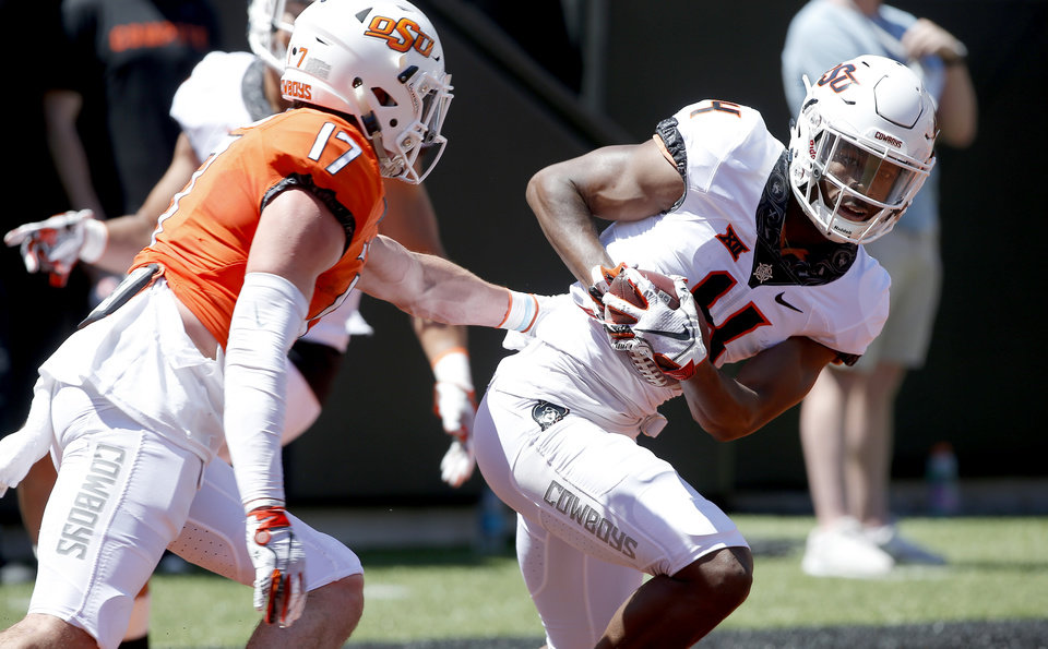 Photo - OSU's A.J. Green makes an interception on a pass intended for Oklahoma State's Dillon Stoner (17) during the Oklahoma State Cowboys spring practice at Boone Pickens Stadium in Stillwater, Okla., Saturday, April 20, 2019.  Photo by Sarah Phipps, The Oklahoman
