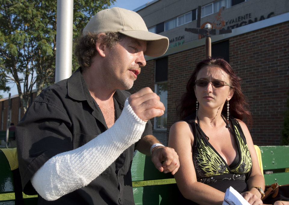 Photo - Bernard Theberge talks about how he escaped from a patio in downtown Lac Megantic, Quebec, when a train derailed sending explosions of railway cars that were carrying crude oil, Saturday, July 6, 2013. Theberge and friend Frederique Marcoux wait outside an emergency center for news of missing friends. T (AP Photo/The Canadian Press, Paul Chiasson)
