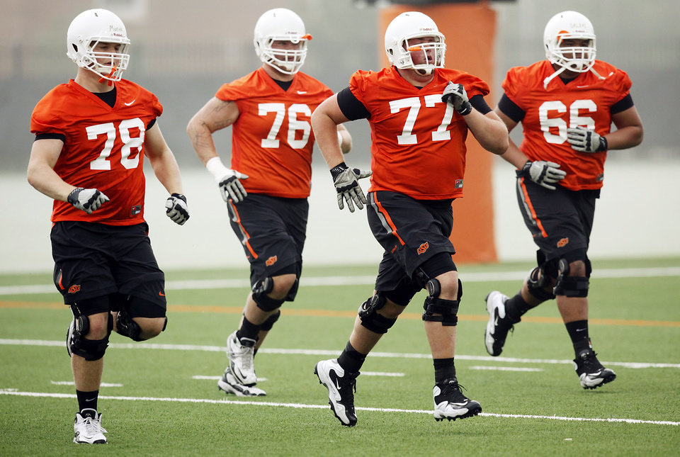 Photo - Oklahoma State offensive lineman Matthew Mucha (78), Colby Hegwood (76), Jaxon Salinas (77) and Lemaefe Galea'i run during the first team practice of the fall at the Sherman E. Smith Training Facility on the campus of Oklahoma State University in Stillwater on August 1, 2014. Photo by KT King, The Oklahoman