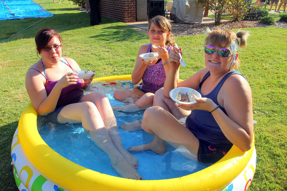 Photo - Jessie Suiter, from Missouri, Tammera Kobriger-Bean, of Yukon, and Elizabeth Evans, of Del City, cool off in a kiddie pool during activities for University of Central Oklahoma students moving on campus.  PHOTO BY HUGH SCOTT, FOR THE OKLAHOMAN