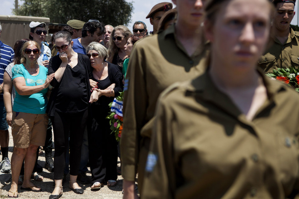 Photo - Family and friends mourn during the funeral of Maj. Tzafrir Bar-Or, 32, one of 13 soldiers killed in several separate incidents in Shijaiyah on Sunday, at the military cemetery in Holon, Israel, Monday, July 21, 2014. On Sunday, the first major ground battle in two weeks of Israel-Hamas fighting exacted a steep price, killing scores of Palestinians and more than a dozen Israeli soldiers and forcing thousands of terrified Palestinian civilians to flee their devastated Shijaiyah neighborhood, which Israel says is a major source for rocket fire against its civilians. (AP Photo/Dan Balilty)