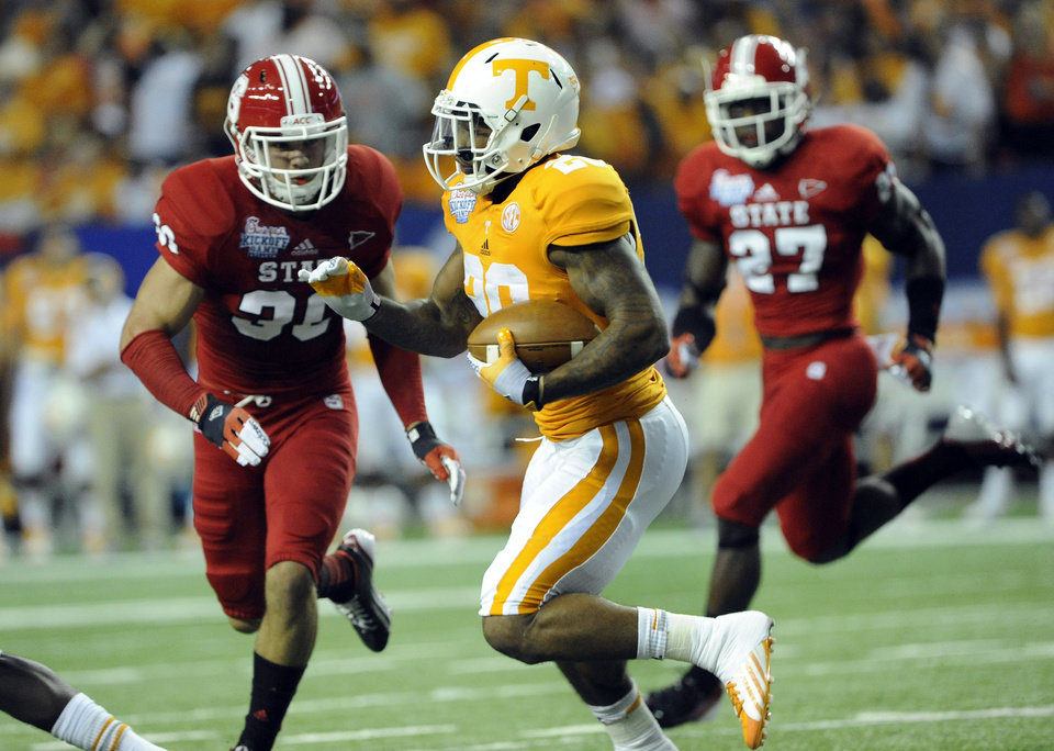 Photo -   Tennessee running back Rajion Neal (20) tries to get by the defense of North Carolina State safety Brandan Bishop (30) and safety Earl Wolff (27) during the first half of the Chick-fil-A Kickoff Game, beginning the NCAA college football season, in Atlanta., on Friday, Aug. 31, 2012. (AP Photo/John Amis)