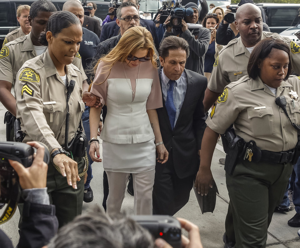 Photo - Actress Lindsay Lohan is escorted by Los Angeles County sheriffs as she arrives for her trial with her attorney Mark Heller, on Monday, March 18, 2013. Lohan is charged with three misdemeanor counts stemming from a crash on Pacific Coast Highway. She is charged with willfully resisting, obstructing or delaying an officer, providing false information to an officer and reckless driving. She is also accused of violating her probation in a misdemeanor jewelry theft case. (AP Photo/Damian Dovarganes)