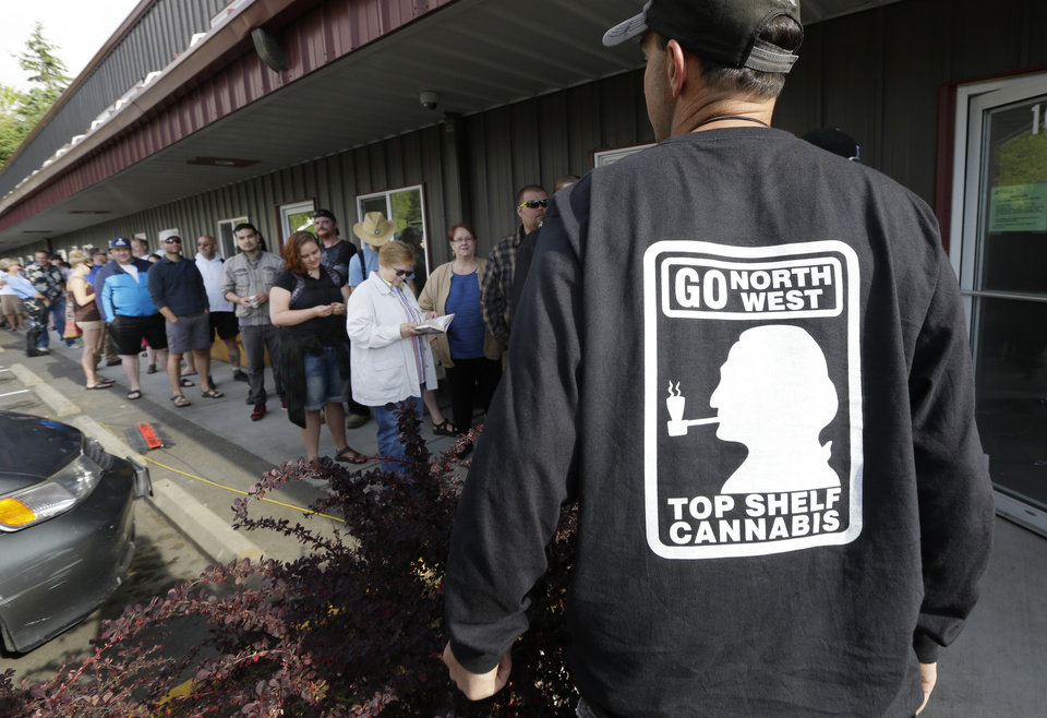 Photo - John Evich, right, an investor in the Top Shelf Cannabis store, talks to customers waiting in line outside the store, Tuesday, July 8, 2014, in Bellingham, Wash., on the first day of legal recreational marijuana sales in the state.  (AP Photo/Ted S. Warren)