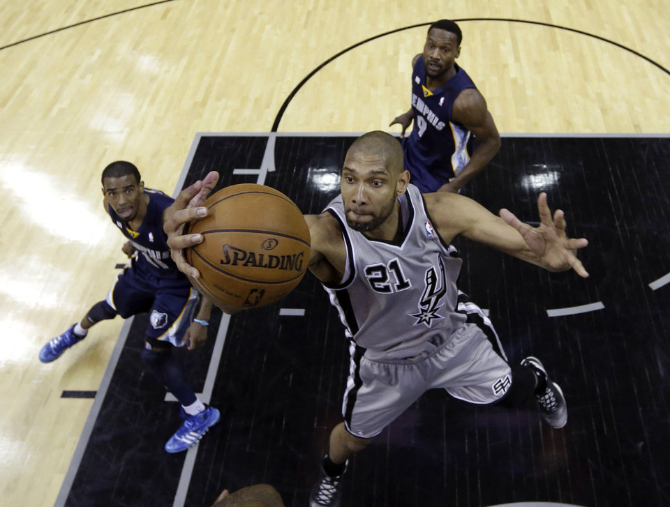 Photo - San Antonio Spurs' Tim Duncan (21) grabs a rebound as Memphis Grizzlies' Mike Conley (11) and Tony Allen (9) look on during the first half in Game 1 of a Western Conference Finals NBA basketball playoff series, Sunday, May 19, 2013, in San Antonio. (AP Photo/Eric Gay)