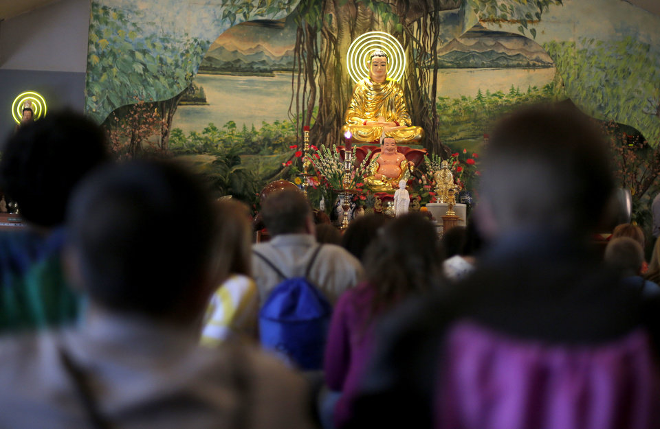 Photo - Youths listen to Buddhist speakers during the Oklahoma Council of Churches' sixth annual Interfaith Youth Tour Sunday at the Vien-Giac Buddhist Temple in Oklahoma City. Photo by SARAH PHIPPS, The Oklahoman