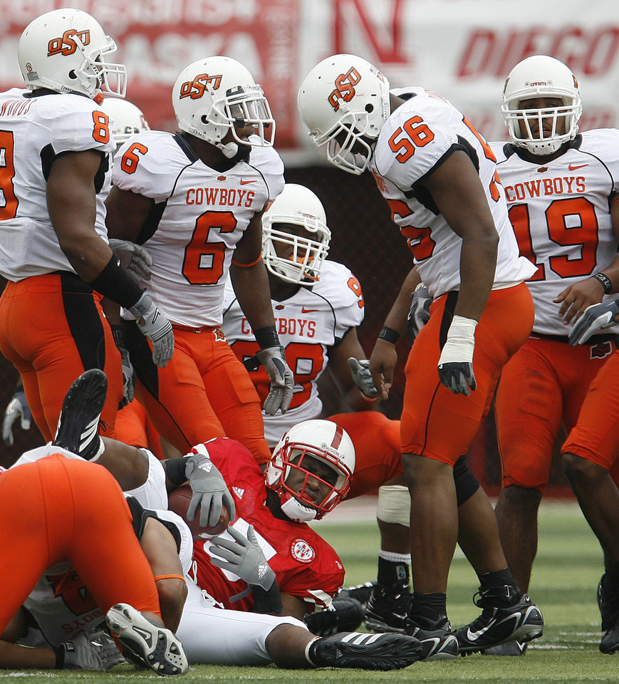 Photo - From left, Donovon Woods, Ricky Price, Derek Burton, Maurice Cummings and Jeremy Nethon of OSU watch as Marlon Lucky of Nebraska get up after a play during  the college football game between Oklahoma State University (OSU) and the University of Nebraska at Memorial Stadium in Lincoln, Neb., on Saturday, Oct. 13, 2007. By Bryan Terry, The Oklahoman