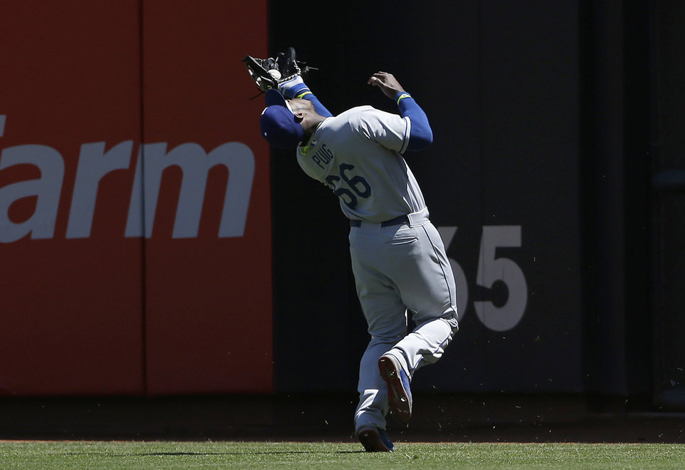 Photo - Los Angeles Dodgers right fielder Yasiel Puig catches a fly ball hit by San Francisco Giants' Gregor Blanco during the second inning of a baseball game in San Francisco, Thursday, April 17, 2014. (AP Photo/Jeff Chiu)