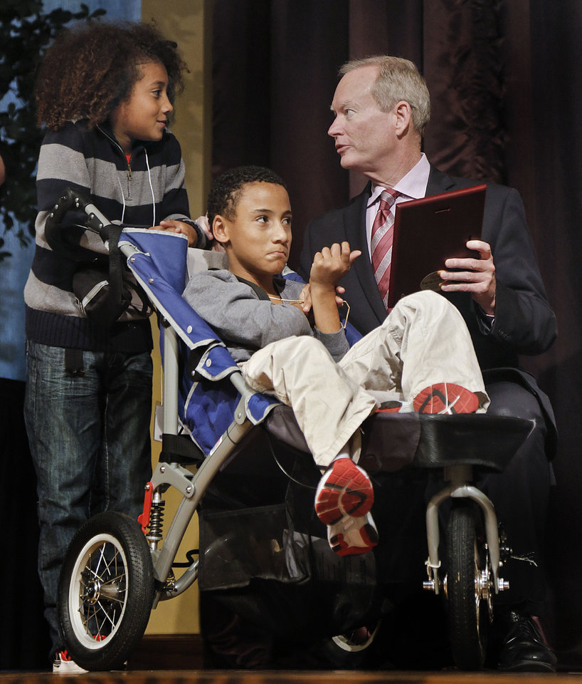 Photo - Mayor Mick Cornett presents Tobias Bass, left, and his brother Titus with a the Special Award Tuesday during the 23rd annual Mayor's Committee on Disability Concerns awards at St. Luke's United Methodist Church in Oklahoma City. Photo by Chris Landsberger, The Oklahoman  CHRIS LANDSBERGER