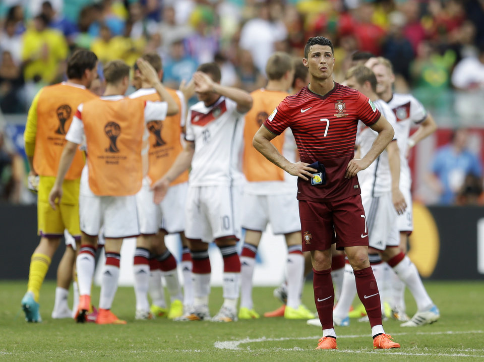 Photo - Portugal's Cristiano Ronaldo stands on the pitch as German players celebrate following Portugal's 4-0 loss to Germany during the group G World Cup soccer match between Germany and Portugal at the Arena Fonte Nova in Salvador, Brazil, Monday, June 16, 2014.  (AP Photo/Natacha Pisarenko)