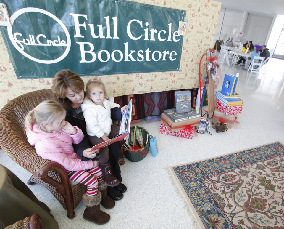 Photo - Beverly Lackey reads a book Friday to her granddaughters Kelsey Lackey, 5, left and Mallory Lackey, 2, at the Full Circle Bookstore pop-up in the Myriad Gardens.  Photo By Steve Gooch, The Oklahoman