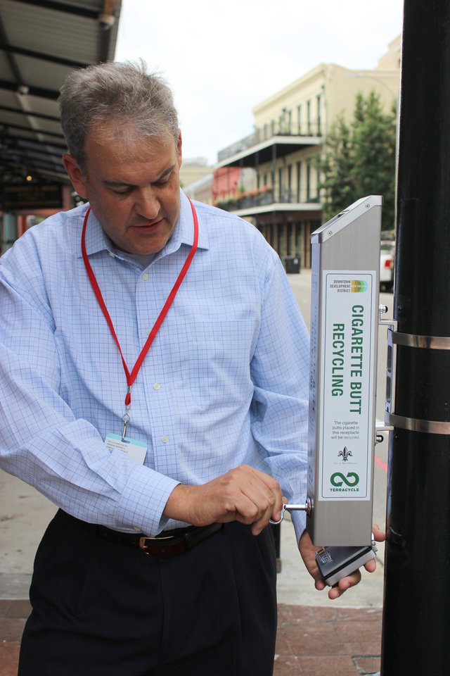 Photo - Richard McCall, operations director of New Orleans' Downtown Development District, shows a container installed, Monday July 21, 2014, to collect cigarette butts for recycling. About 50 will be installed in areas with heavy pedestrian traffic.  TerraCycle Inc. will donate $4 to the city for every pound of butts sent to its recycling plant in Trenton, New Jersey. (AP Photo/Janet McConnaughey)