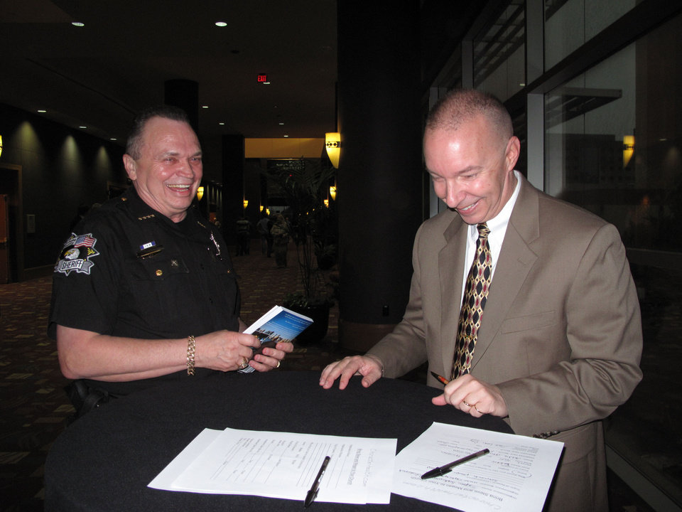 Photo - Oklahoma County Sheriff John Whetsel talks with Steve Scheibner as Scheibner signs a copy of the book