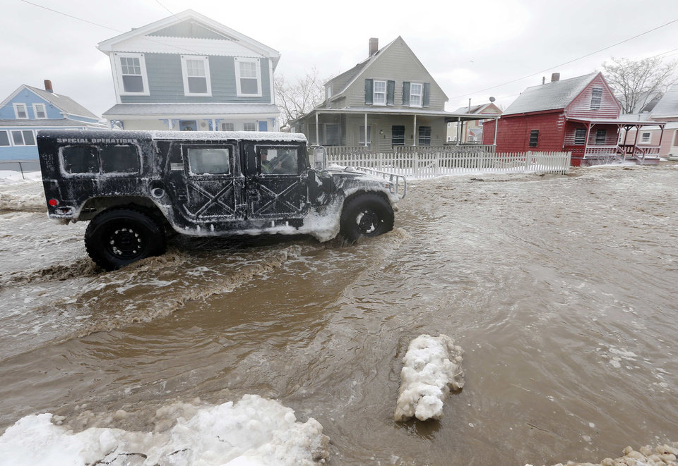 Photo - A police special operations vehicle drives down a flooded street along the shore in Hull, Mass., Friday, Jan. 3, 2014, in the wake of a winter storm.  (AP Photo/Michael Dwyer)