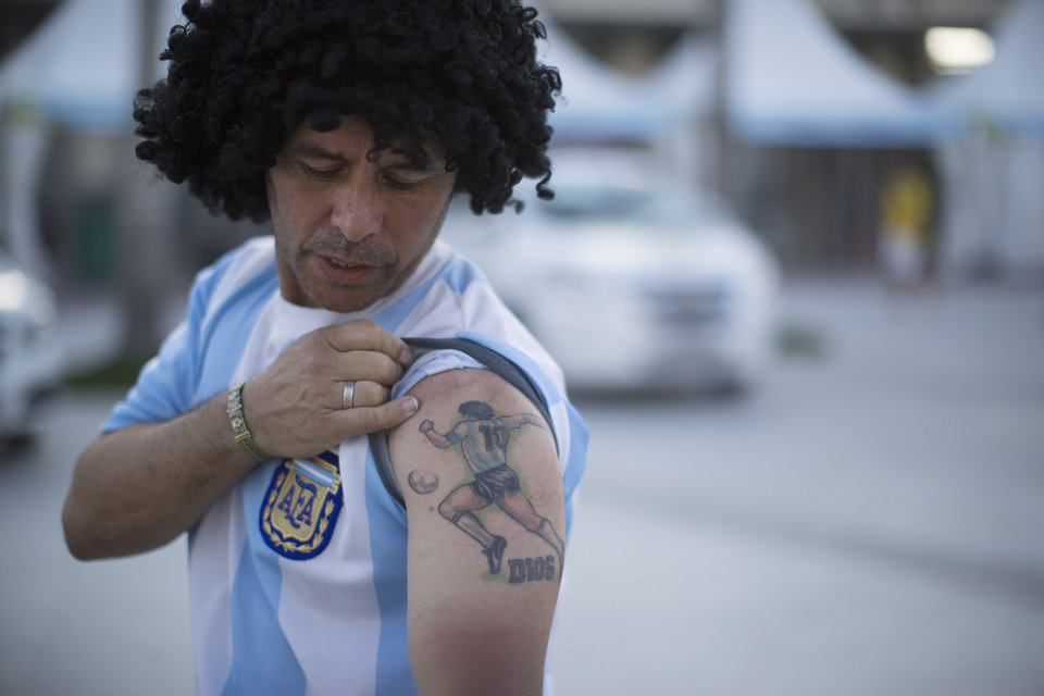 Photo - Street performing mime, Daniel Gonzalez, 35, who is dressed to resemble Argentine soccer great Maradona, shows his tattoo with the image of the argentine soccer player and the word God in Spanish underneath, in front of Maracana stadium, Rio de Janeiro, Brazil, Wednesday, June 11, 2014. The World Cup soccer tournament starts Thursday. (AP Photo/Leo Correa)