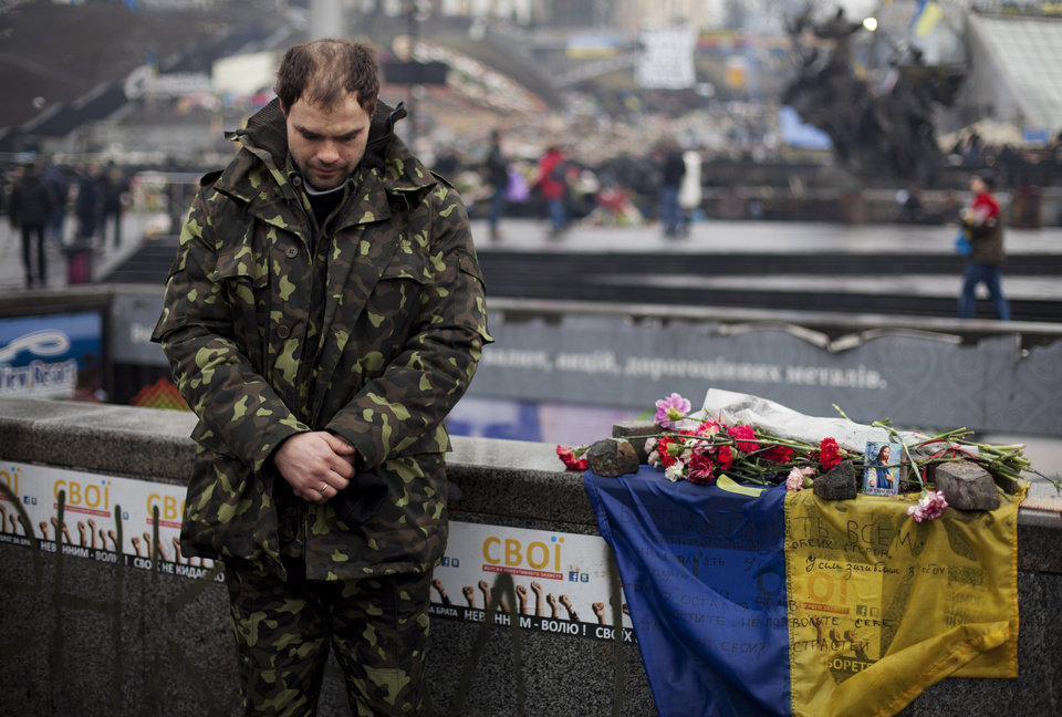 Photo - A Ukrainian self defense volunteer bows his head during a funeral ceremony for Andryi Pozniak, 25, who was also a self defense volunteer and who was shot and killed by an unknown assailant two days ago near Kiev's Independence Square, Ukraine, Thursday, March 6, 2014. (AP Photo/David Azia)