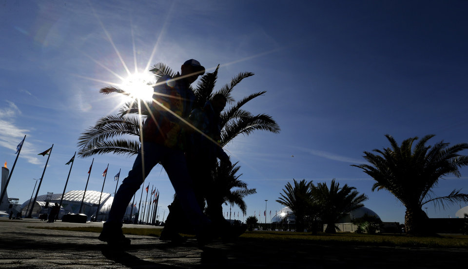 Photo - Visitors to the Olympic Park pass by palm trees on a warm sunny dat at the 2014 Winter Olympics, Wednesday, Feb. 12, 2014, in Sochi, Russia. (AP Photo/David J. Phillip )
