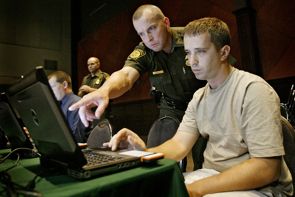 Photo - Border Patrol agent Lee Jayroe talks with Brian Frutchey as he fills out a job application during the military job fair at the Coca-Cola Events Center on Thursday, July 31, 2008, in Oklahoma City, Okla.   Staff Photo By CHRIS LANDSBERGER ORG XMIT: KOD