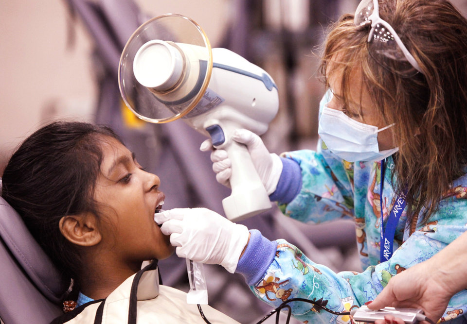 Photo - Manasa Lagisetty, 8,  has her teeth   X-rayed by  Dena Woods, a dental assistant.   More than 1100 people came to the Cox Convention Center Friday,  Feb. 4, 201!, to receive free dental care as the two day traveling dental clinic opened for clients in Oklahoma City.  The clinic is sponsored by Delta Dental and Oklahoma Mission of Mercy.     Photo by Jim Beckel, The Oklahoman Archives.