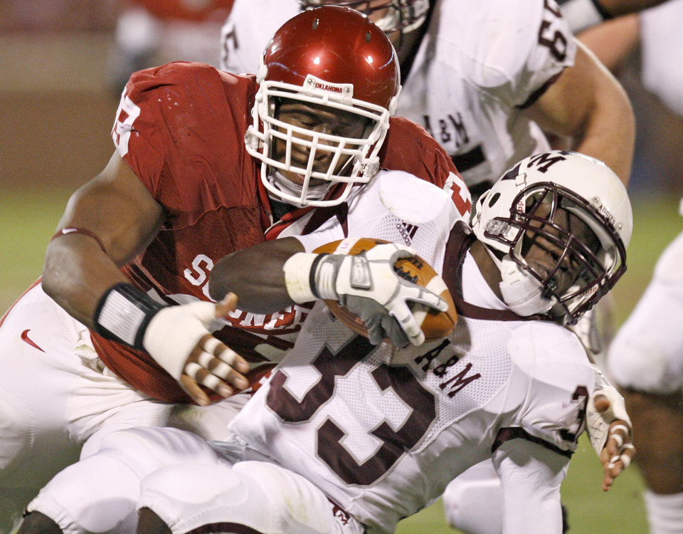 Photo - OU's Gerald McCoy brings down Texas A&M's Christine Michael during the Big 12 college football game between the University of Oklahoma Sooners and the Texas A&M Aggies at Gaylord Family - Oklahoma Memorial Stadium in Norman, Okla., Saturday, November 14, 2009.  Photo by Bryan Terry, The Oklahoman