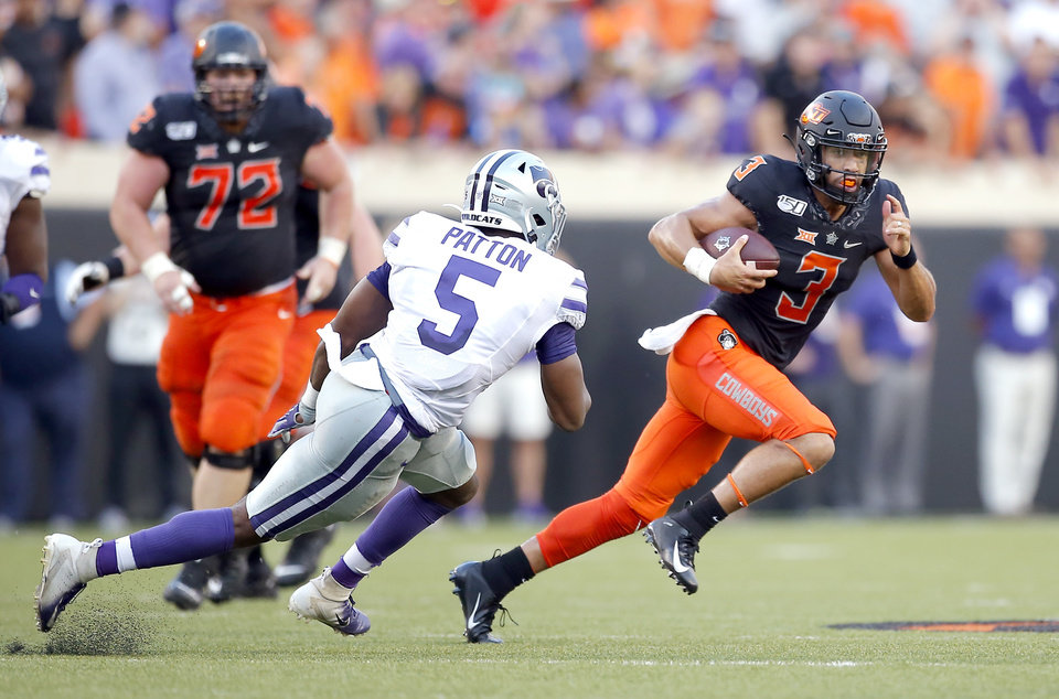 Photo - Oklahoma State's Spencer Sanders (3) looks to get by Kansas State's Da'Quan Patton (5) during the college football game between the Oklahoma State Cowboys and the Kansas State Wildcats at Boone Pickens Stadium in Stillwater, Okla., Friday, Sept. 27, 2019. [Sarah Phipps/The Oklahoman]