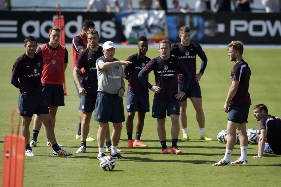 Photo - England's manager Roy Hodgson, fourth left, instructs his players including Frank Lampard, left, and Wayne Rooney, fourth right, during a squad training session for the 2014 soccer World Cup at the Urca military base in Rio de Janeiro, Brazil, Monday, June 9, 2014.  (AP Photo/Matt Dunham)