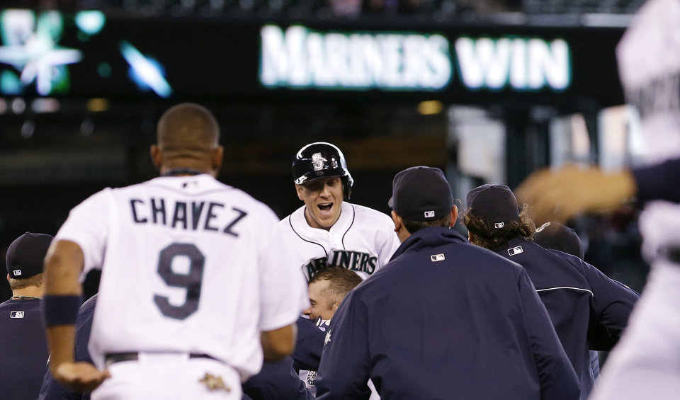 Seattle Mariners' Jason Bay, center, is mobbed by teammates after his single scored the winning run against the Texas Rangers in the 13th inning in a baseball game on Sunday, May 26, 2013, in Seattle. The Mariners won 4-3. (AP Photo/Elaine Thompson)