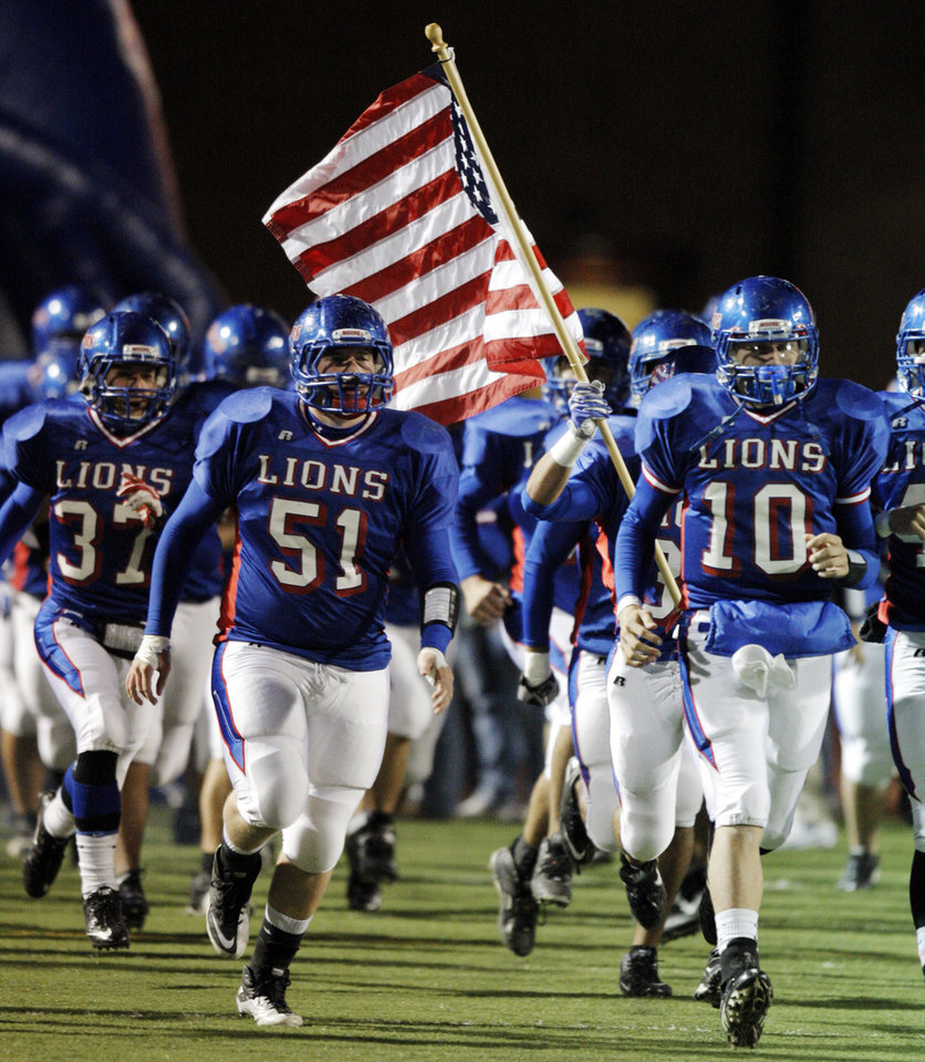 Photo - The Moore Lions take the field before a 2010 game against Lawton Eisenhower. Photo by Nate Billings, The Oklahoman Archives