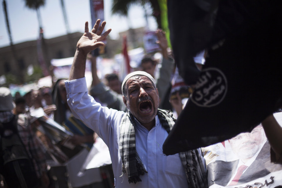 Photo - A supporter of Egypt's ousted President Mohammed Morsi chants slogans against the army during a protest Cairo University, in Giza, Egypt, Friday, July 26, 2013. Egyptian prosecutors accused ousted President Mohammed Morsi on Friday of conspiring with the Palestinian militant group Hamas and murder in his 2011 escape from prison that left 14 guards dead. The development fueled the likelihood of clashes as tens of thousands of supporters and opponents of the Islamist leader massed for rival rallies. (AP Photo/Manu Brabo)