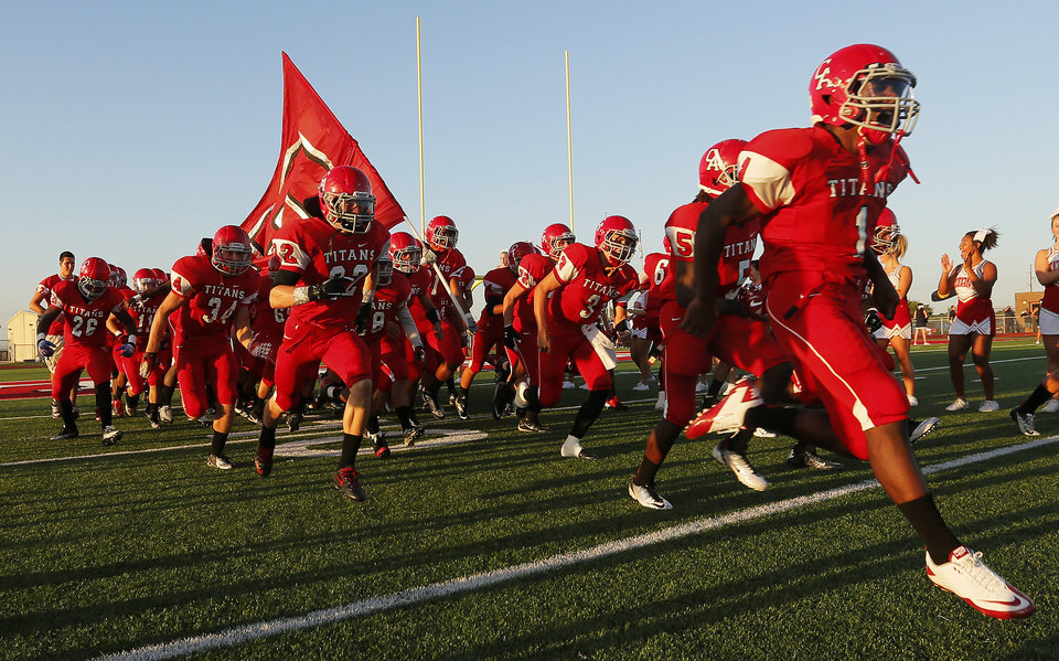 Photo - The Carl Albert Titans take the field before a high school football game between Carl Albert and Southmoore in Midwest City, Okla., Friday, Aug. 31, 2012. Photo by Nate Billings, The Oklahoman