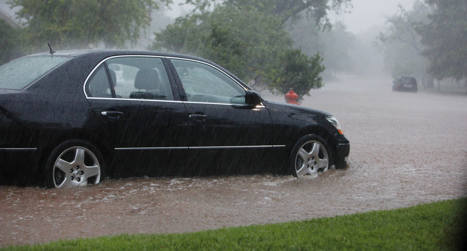 Photo - A car stranded in high water during heavy rains on Waverly Ave.  at Wilshire Blvd. in Nichols Hills Monday, June 14, 2010. Photo by Paul B. Southerland, The Oklahoman