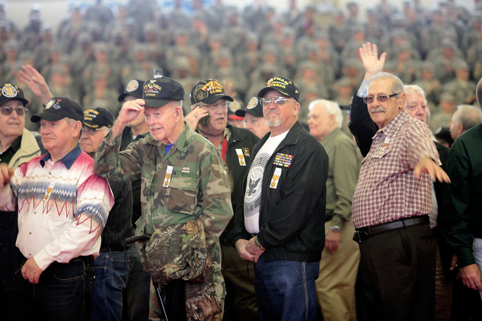 Vietnam veterans wave Friday as they walk into the Rinehart Fitness Center at Fort Sill to a standing ovation for a welcoming home ceremony. Photo By David McDaniel, The Oklahoman